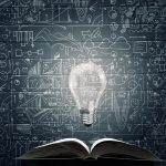 Old opened book with glass bulb and business strategy sketches